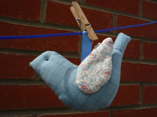 Stitched bird pegged to clothes line