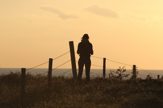 Silhouette of Bryony and fence on clifftop