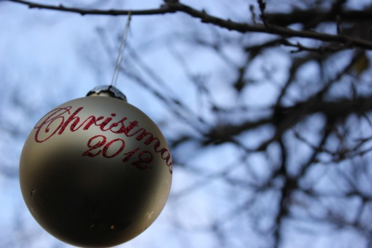 Looking up at gold christmas bauble in tree