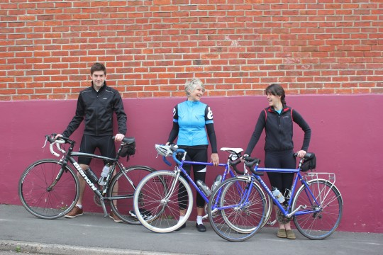 Alec, Wendy and Bryony with their bikes against a wall