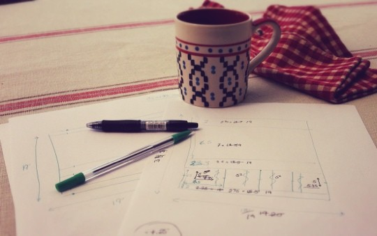 Paper plans next to mug of coffee