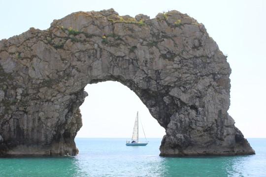 Yacht visible through Durdle Door rock