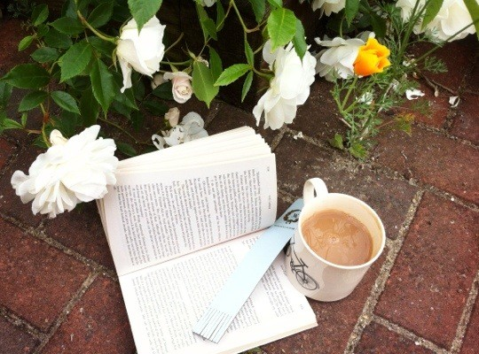 Open book and cup of tea on the paving