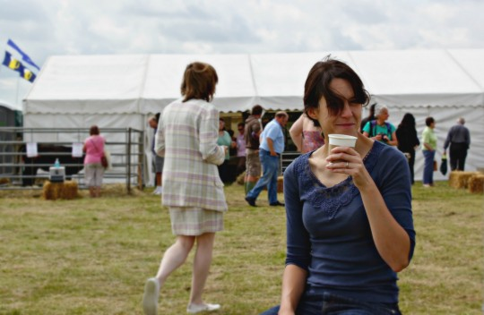 Bryony drinking coffee outside a marquee