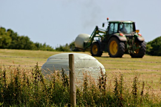 Fence, hay bale and tractor