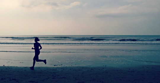 Bryony running on beach with sea in background