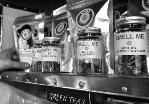 Smell me tea jars on a shelf in black and white