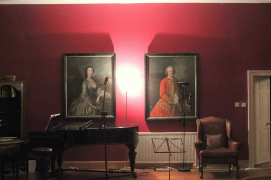 Grand piano and armchair with classic oil paintings