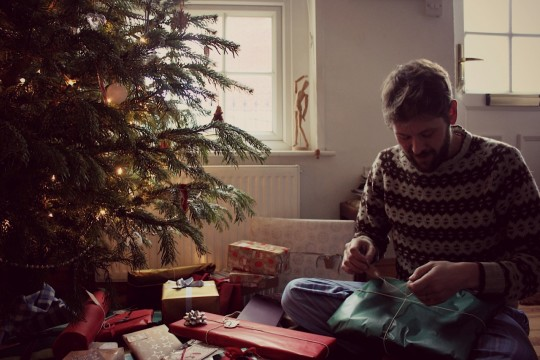 Tom opening presents by the Christmas tree