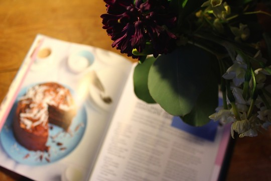 Cookbook open next to flowers