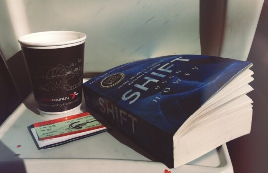 Coffee cup and book on the train