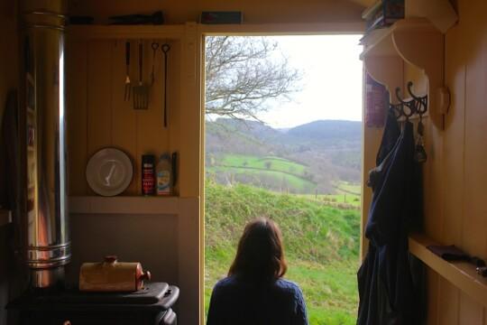 Rusty sitting in the doorway of a shepherd's hut