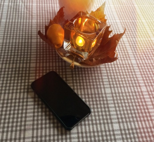 iPhone on table next to candle