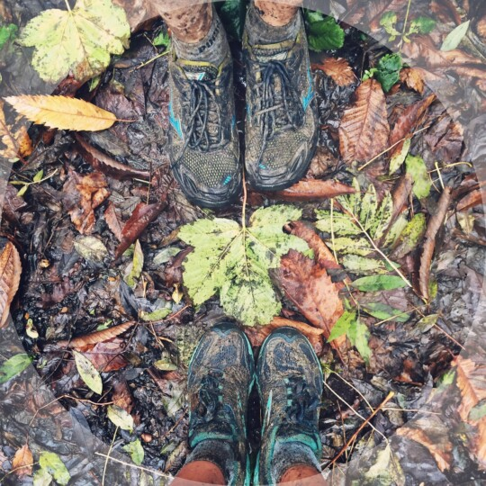 Looking down at muddy running shoes