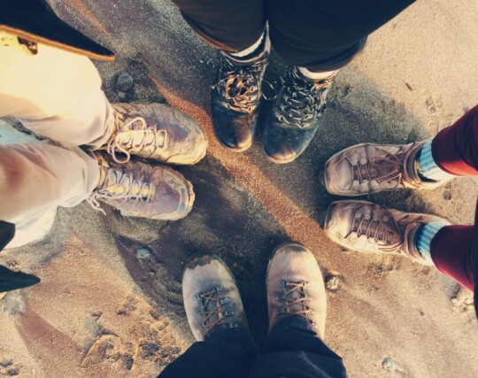 Looking down at 4 pairs of boots on the beach