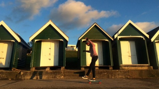 Penny boarding past beach huts