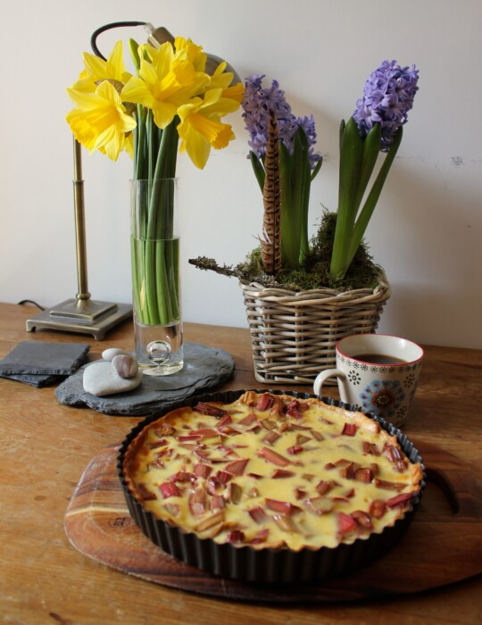 Rhubarb tart on table next to flowers