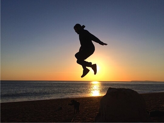 Tom jumping on a beach at sunset