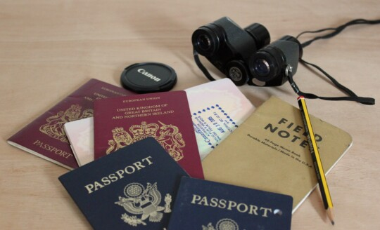 Passports, notebook, binoculars and pencil on table